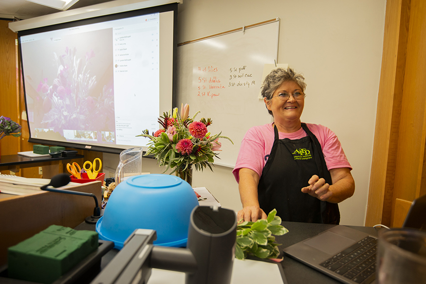 MSU floral management instructor Lynette McDougald smiles while standing near a bouquet of bright pink flowers in a classroom.