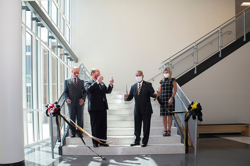 Administrators cut a ribbon in the atrium of the Partnership Middle School