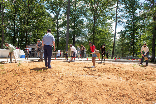Attendees turn dirt during a Monday [Aug. 3] groundbreaking ceremony at the site of the 12th annual Maroon Edition home.