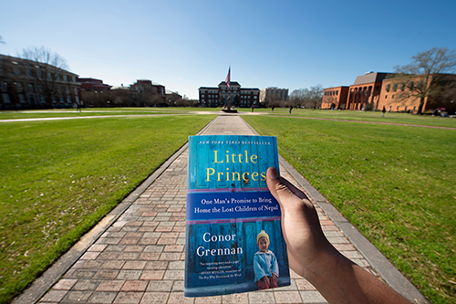"2020 Maroon Edition book, ""Little Princes: One Man's Promise to Bring Home the Lost Children of Nepal,"" held by student on the Drill Field"