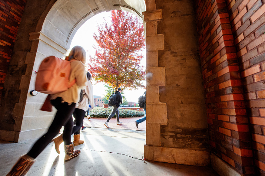 A student walks under the arch at McCain Hall on a crisp fall day.