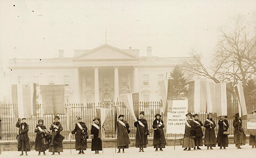 A vintage, sepia-toned photo shows members of the National Woman's Party picketing in front of The White House