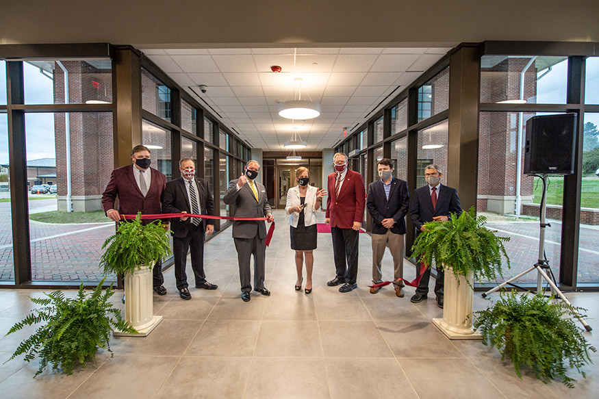 Seven MSU administrators and partners stand in a new building during a ribbon-cutting ceremony