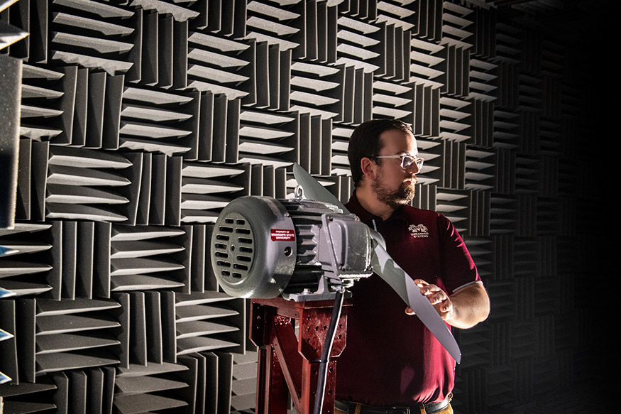 Raspet Flight Research Laboratory engineer Hunter Vesa grasps a propeller while standing inside the acoustic anechoic chamber