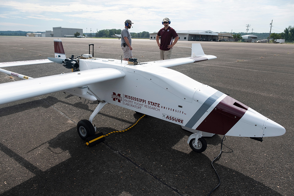 Raspet personnel prepare to fly an unmanned aircraft on an airport runway.