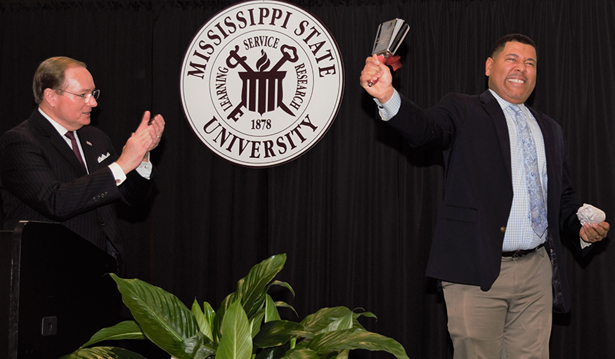 A man applauds as another rings a cowbell with the MSU seal in the background.
