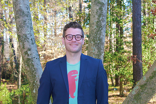 A man is pictured wearing glasses and a blazer and T-shirt with a wooded area in the background