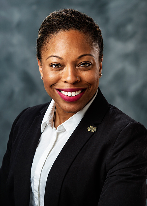 Studio portrait of Shandrea Stallworth wearing a business coat in front of a gray background