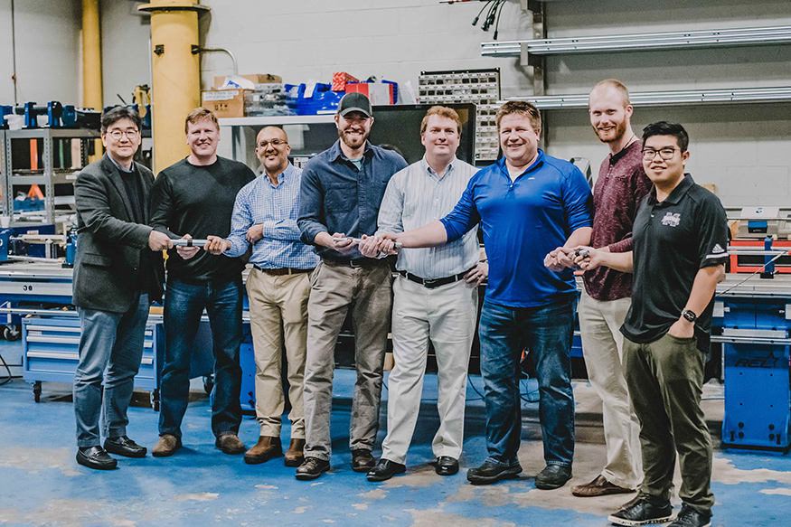 MSU and REL personnel pose with their serpentine bar technology.