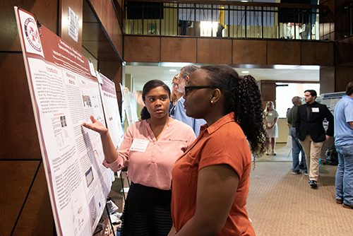"Jordan S. Bryant, an incoming freshman chemistry major from Porterville, speaks with a judge during Mississippi State's Summer Undergraduate Research Symposium. For her research project titled ""NIH R25 Bridges to Baccalaureate,"" Bryant has been advised by Krish Krishnan, associate professor in the university's Department of Biochemistry, Molecular Biology, Entomology and Plant Pathology. (Photo by Colleen McInnis)"