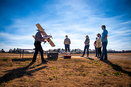 Amelia Fox (far left), assistant clinical professor in the MSU Department of Plant and Soil Sciences, readies the fixed-wing E-flite Timber Apprentice for flight while students and colleagues look on.