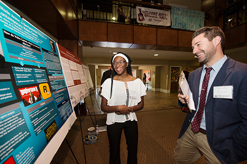 "Junior biochemistry major Auriana P. Tucker of Brookhaven explains her research project ""Grimms Tales Made Anew: A Benjaminian Analysis of Contemporary Video Games"" to Assistant Professor of English Eric Vivier during Mississippi State University's Spring Undergraduate Research Symposium. (Photo by Megan Bean)"