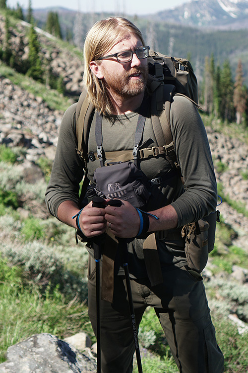 Brandon Barton on a research expedition dressed in hiking gear outdoors.