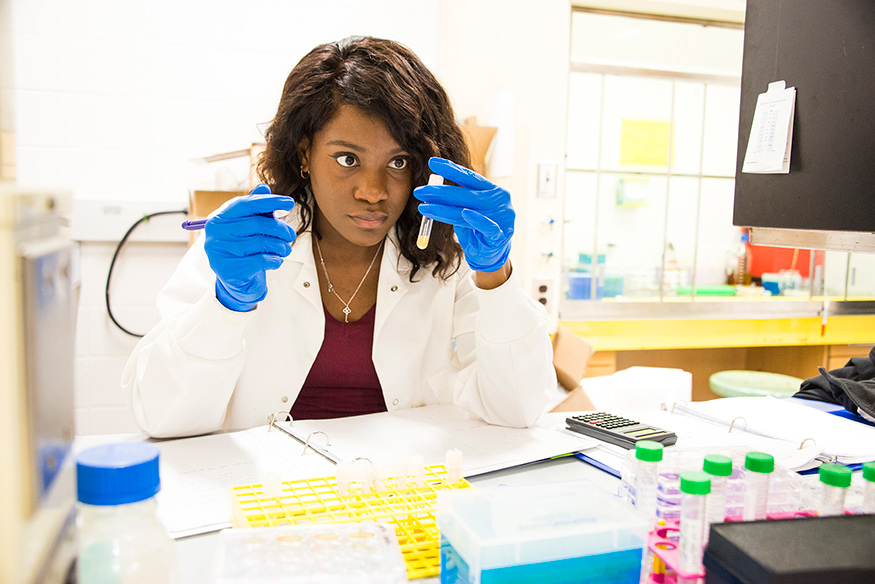 A young woman looks at test tubes in a biochemistry lab.