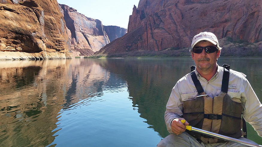 Wes Burger canoeing on the Colorado River with river and canyons in the background