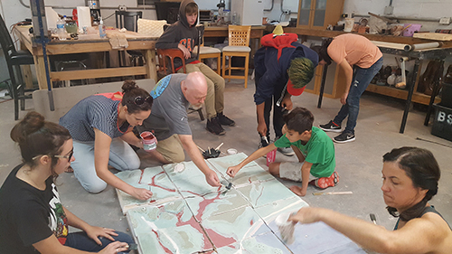 Youth from the Hancock County Unit of the Boys and Girls Club worked with community artists on a 3D tile model of the Magnolia Bayou watershed. The tile model became part of a multi-media art exhibition in Bay St. Louis highlighting watershed dynamics, water quality and quantity, and watershed planning and action. (Photo courtesy of MSU Gulf Coast Community Design Studio)