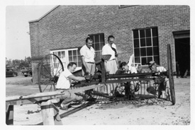 Early black and white photo of MSU students working on farm equipment.