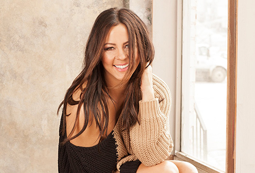Sara Evans smiles for the camera while seated near a window.